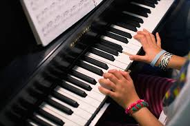 Image of hands playing a piano